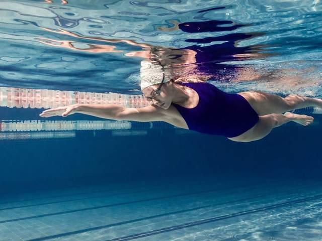 Frau krault im Schwimmbad