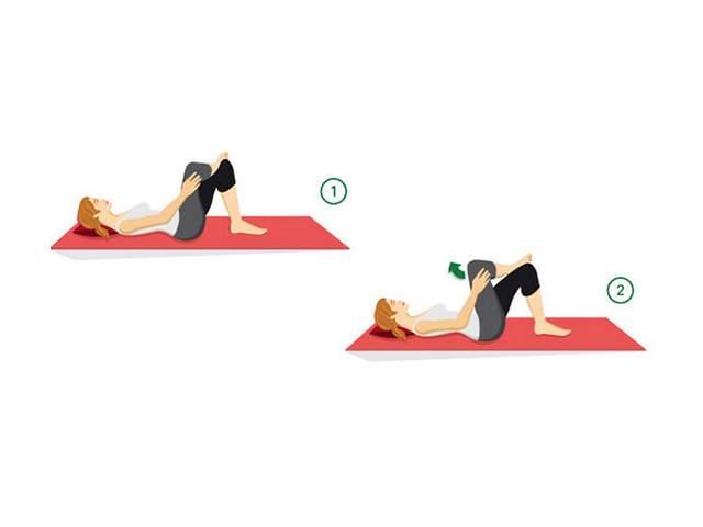 Frau leigt auf Rücken dehnt die Gesäßmuskulatur