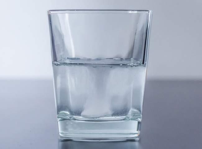 Magnesium Braustablette löst sich in Glas voller Wasser auf