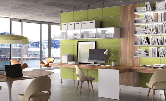 Interior of an office space. A wooden section sits between two green System 1224 walls with the shelves carrying books and boxes. Wooden desks are organized around the room with tan colored chairs.