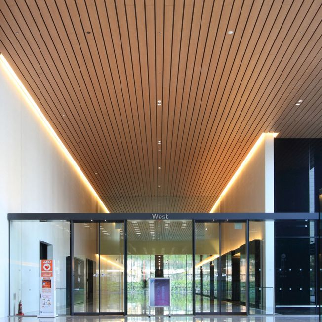 Fortina panels are laid across the ceiling of the interior of a building. Lights are light up the ends of the walls.