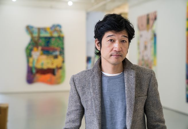 artist Tomokazu Matsuyama standing in his studio and looking to the camera