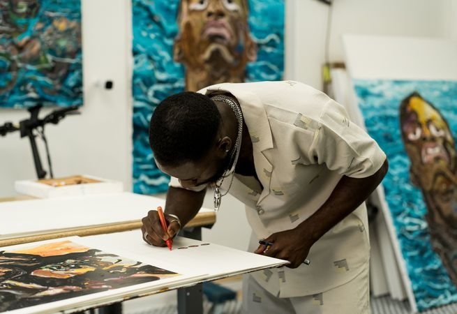 artist Ludovic Nkoth hand-finishing his print in his studio