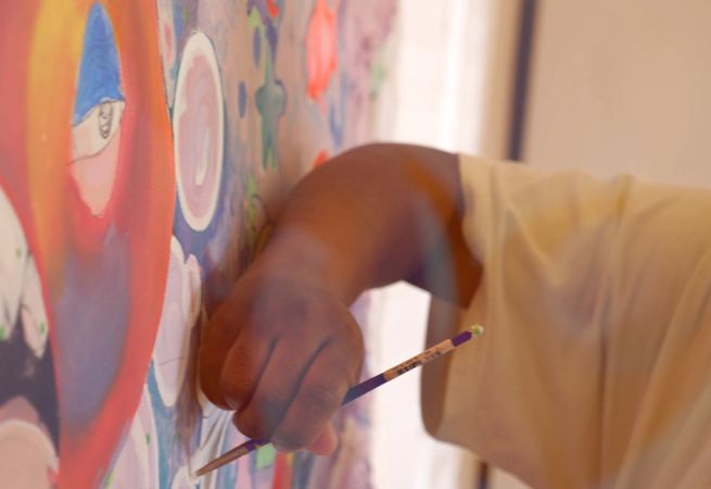 artist holding paint brush up to a colourful painting on the wall