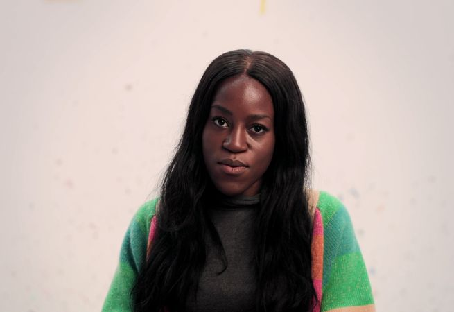 a woman wearing a colourful cardigan sitting down and looking into the camera