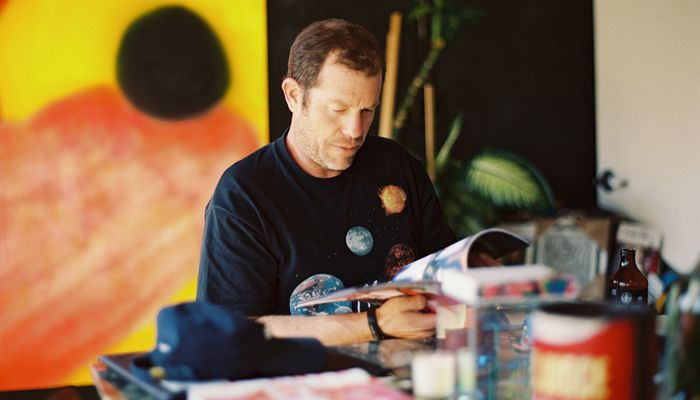 A close up shot of Darren Romanalli sitting in his studio and looking through a book