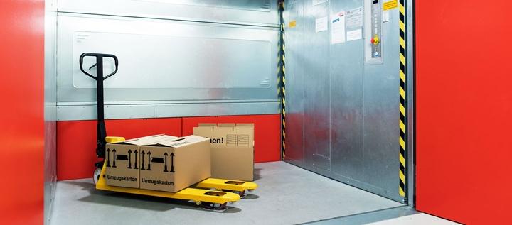 Hubwagen mit Umzugskartons in Lastenaufzug