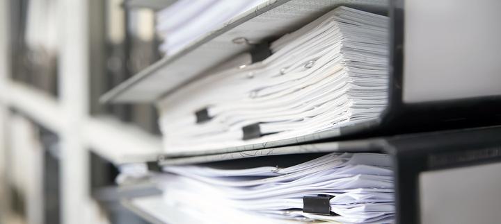 Ordner mit Dokumenten in einem Regal