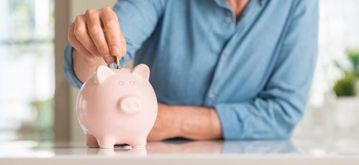 Mann tut Geld in Sparschwein