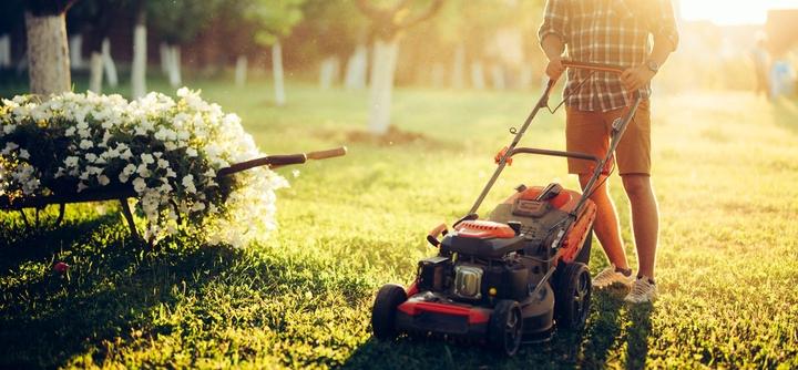 Mann beim Rasenmähen in Berlin