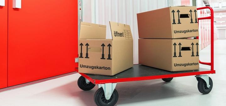 Rollwagen mit Umzugskartons vor Lagerraum