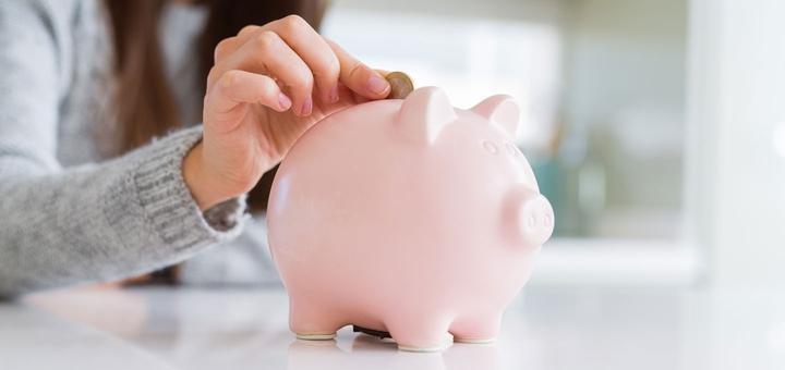 Frau steckt Geld in Sparschwein