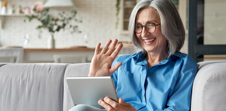 Frau nutzt Tablet auf Sofa