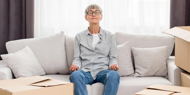 Ältere Frau meditiert auf Sofa