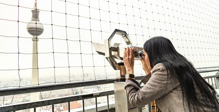 Frau schaut durch Fernglas auf Berliner Fernsehturm