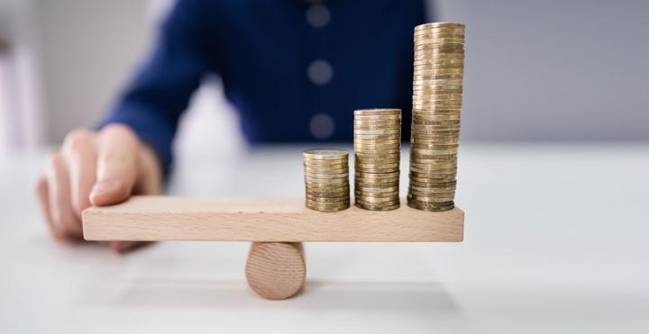 Mann balanciert Münzen auf selbst gemachter Wippe
