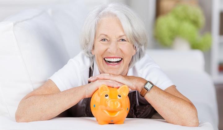Frau lehnt glücklich über einem Sparschwein