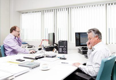 Two men in an office talking to customers on the phone