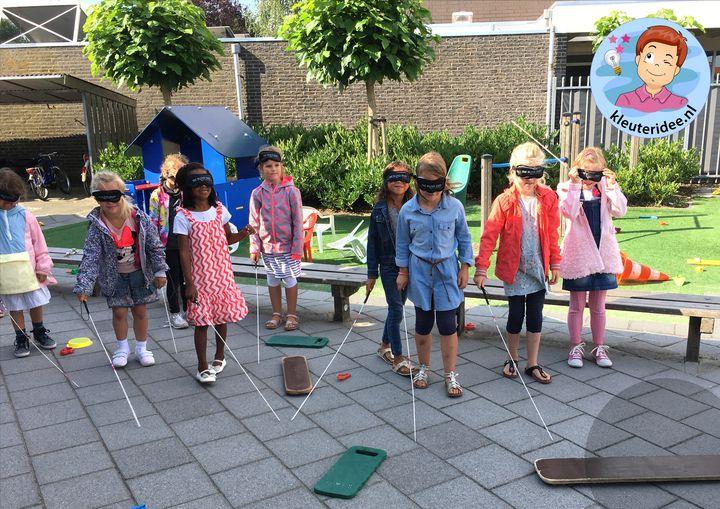 kleuters lopen met zelfgemaakte blindenstok, kleuteridee, thema het oog