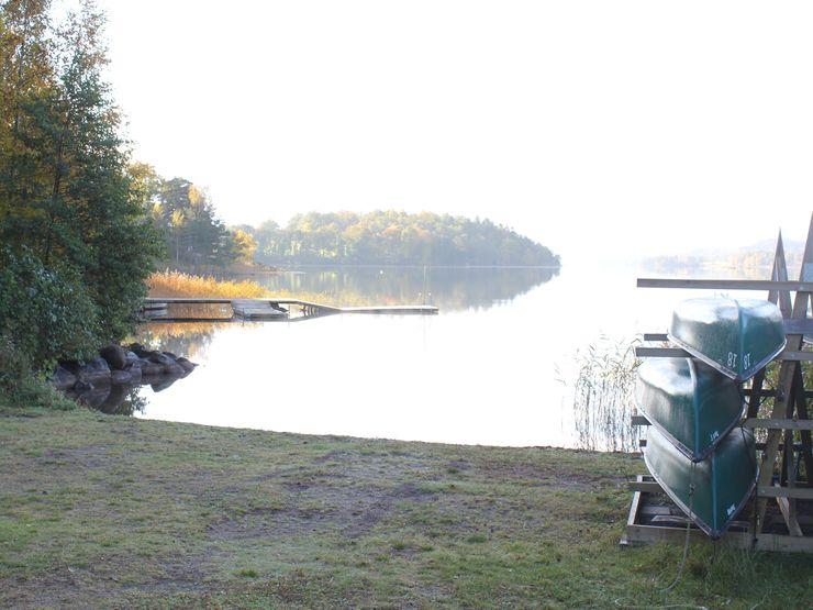 Sjön Åsunden spegelbild i vatten och kanoter