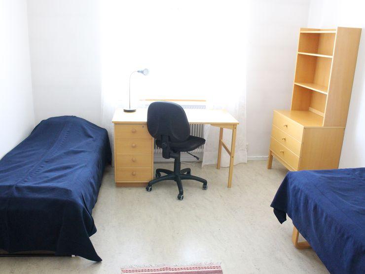 Evagården rum med säng, skrivbord och hylla