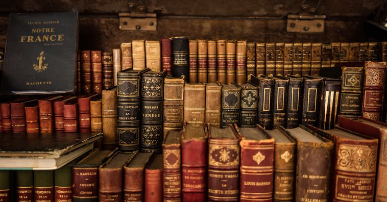 antique books stacked on a shelf