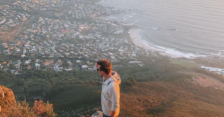 traveler standing on cliff overlooking coast of cape town at sunset