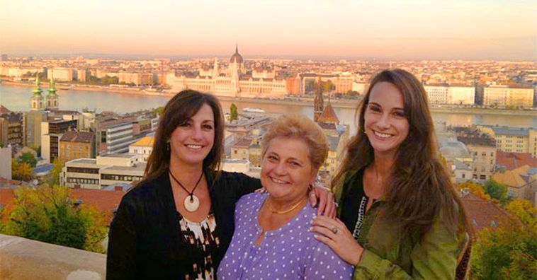 three travelers standing together with city view of budapest at sunset