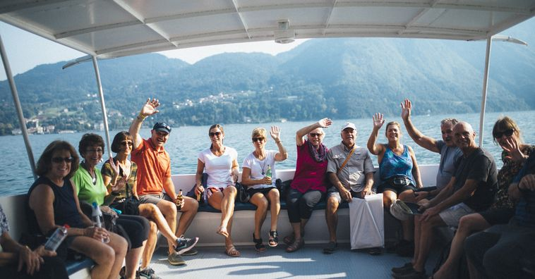 group of travelers waving at the camera from a boat on lake como in italy
