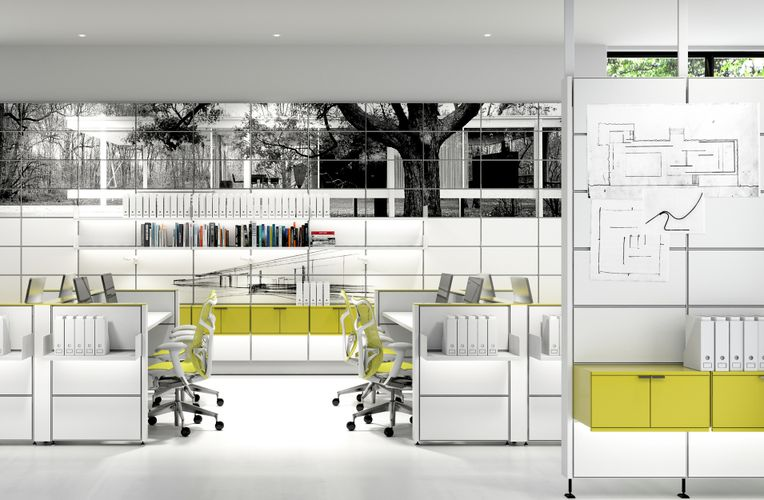 View of an interior space of a white office. White and lime colored chairs are paired with white desks within the room. The back wall is made up of white panels with the top few rows of panels consisting of a printed black and white image of an outdoor space. Along the wall white System 1224 shelves are holding up various books and white binders.