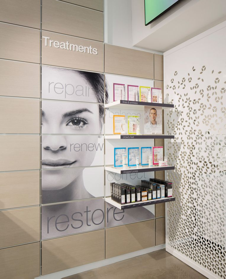 Close up image of one of the walls within Murad. A close-up shot of a woman's face is printed across panels with white System 1224 shelves showcasing a variety of skincare products.