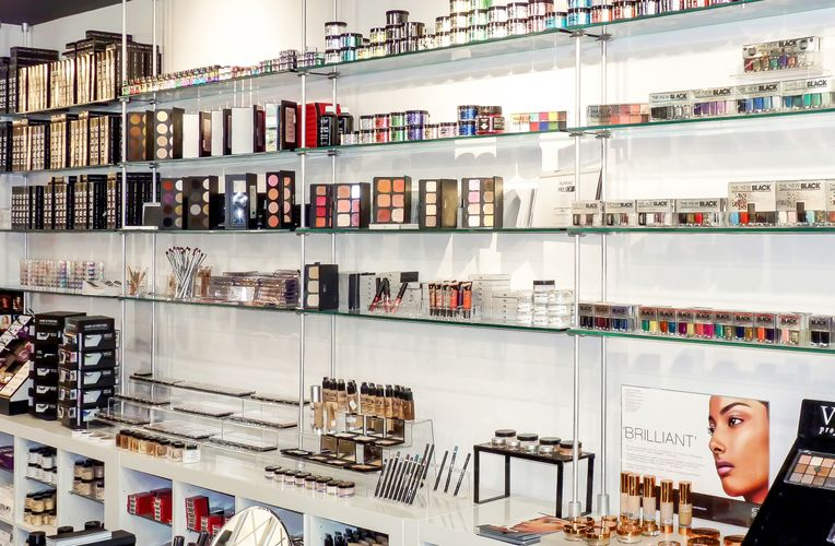 Many different makeup products are lined up neatly against glass shelves held up by cables and rods.