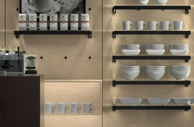 Close-up shot of a wall from a coffee shop. On a light wooden wall, various black shelves are propped up using the Puck system. The shelves display various white ceramic wares as well as coffee bean bags.