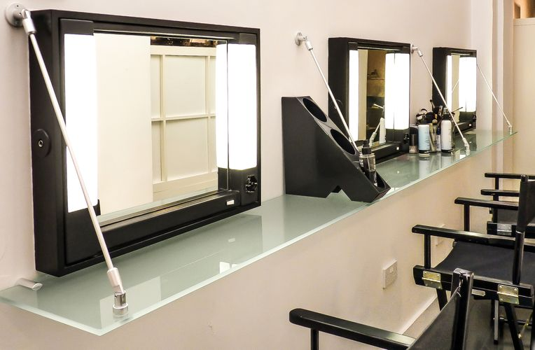 Three mirrors with opaque glass shelves lined up perpendicular to them using cables and rods are lined up against the wall.