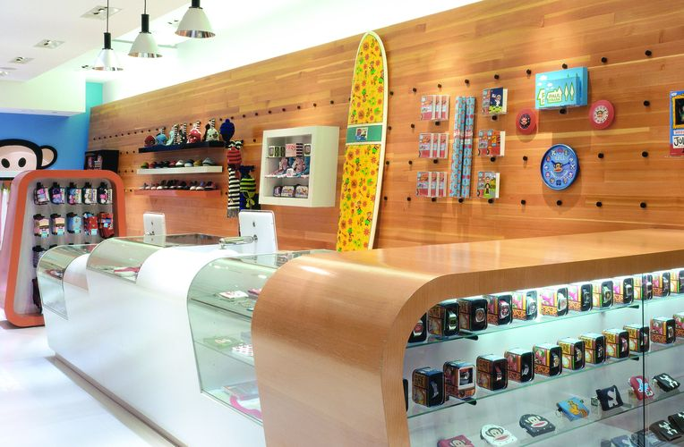 Interior view of a counter at a Paul Frank store. Wooden and glass display tables are lined against a white and glass counter. The back wall is wooden and displaying various Paul Frank merchandise through the Puck system including a large yellow surfboard and a blue clock.