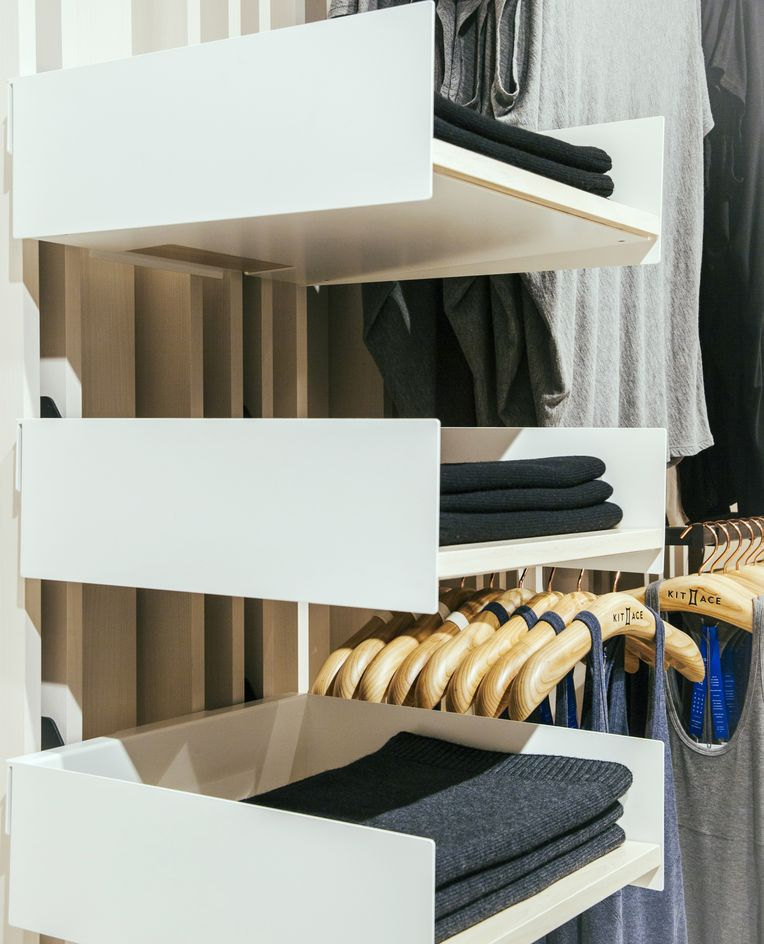 Close-up shot of three of the white System 1224 shelves, each holding different stacks of neatly folded clothes.