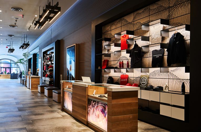 Interior view of Planet 13 equipped with dotted Infused Veneer panels and black System 1224 shelves displaying Planet 13 merchandise.