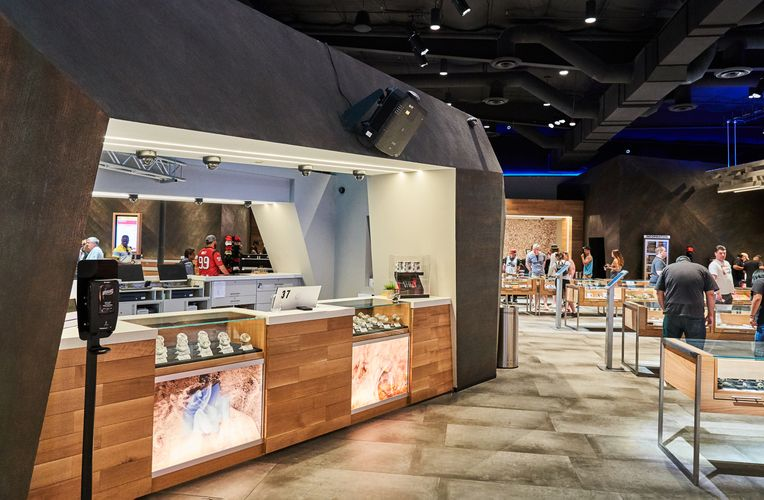 A view of the interior of Planet 13. A large stone stand stands prominently in the center with wooden and glass display tables lined next to it.