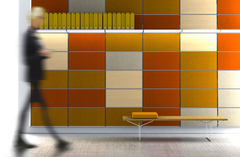 An orange-themed paneled wall. White System 1224 shelves are placed along the top, carrying yellow binders. A wooden bench sits at the bottom with an orange binder placed on top. On the left is a blurred view of a man walking past the wall.