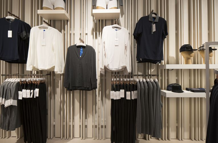 Close up of a Kit and Ace store wall equipped with warm Fortina panels and white System 1224 shelves, both showcasing a variety of different clothes.
