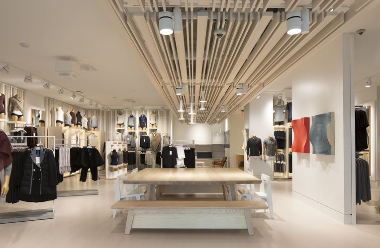 View of Kit and Ace store equipped with warm Fortina panels and White Ash System 1224 Shelves, showcasing a variety of different clothes.
