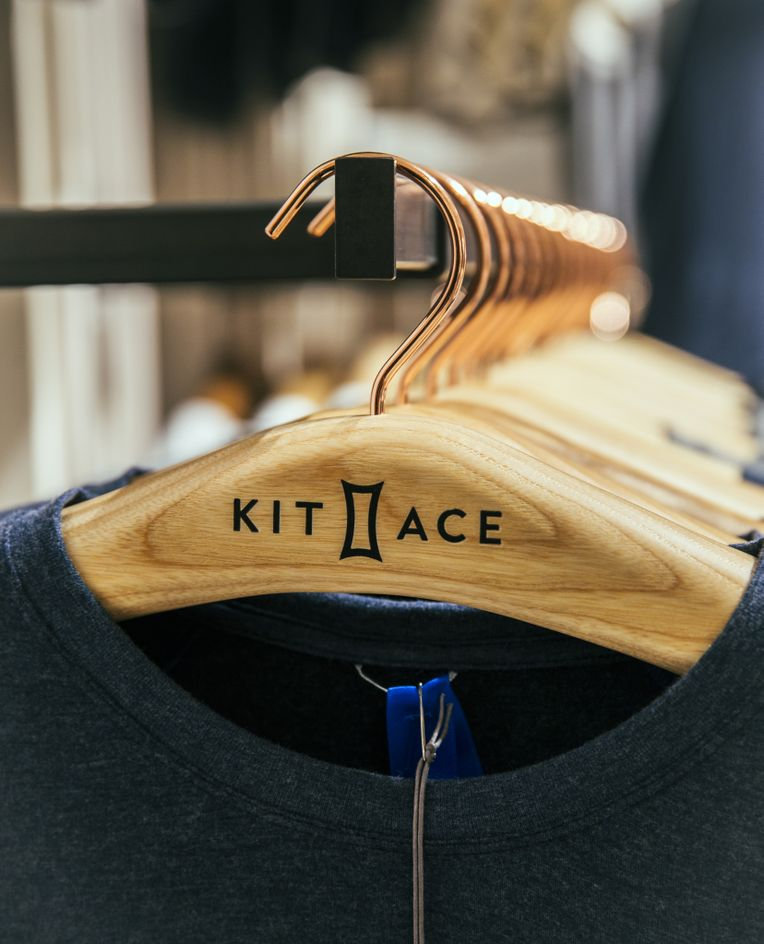 A close-up shot of one of Kit and Ace's wooden clothes hangers, labelled with the Kit and Ace logo.