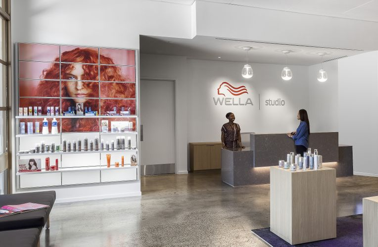 Various beauty products are on display on wooden blocks on the floor as well as on the white System 1224 shelves along the wall. A red image of a woman is printed on lit panels along one of the walls.