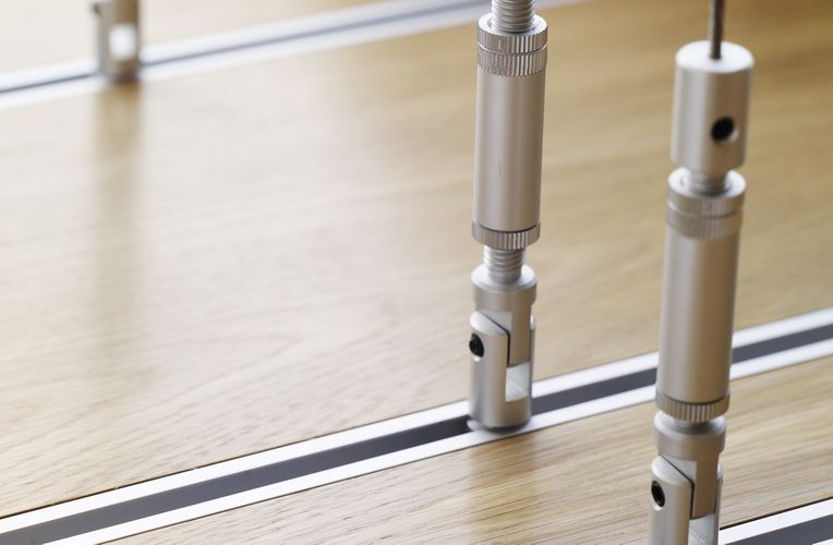 Close-up view of metal rods wedged between metal lines that run horizontally across a wood board.