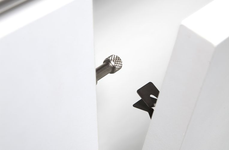 Close-up of two white pieces—one with a metal extension and the other with a black clasp—about to meet each other.