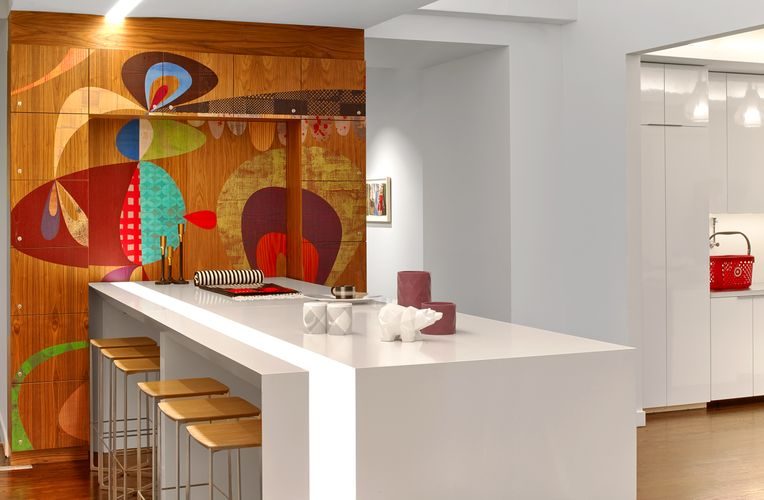 A colorful patterned Infused Veneer panel is used to decorate a white space furnished with wooden stools.