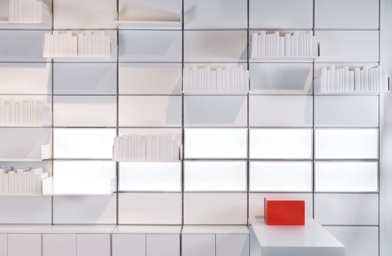 Multiple white System 1224 shelves carrying white books are propped against a white paneled wall. A long white table at the bottom holds two large red boxes that contrast amidst all the white.