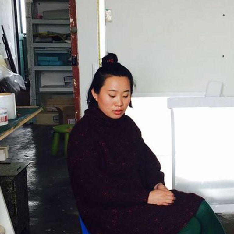 Artist Zhang Ruyi sitting in the studio