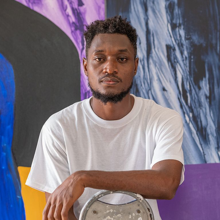 Isshaq Ismail sitting on a chair with his hand resting on it in front of him as he stares forwards towards the camera