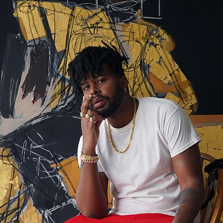 Portrait photograph of Ferrari Sheppard sat in front of his painting looking towards the camera